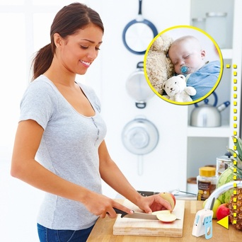 Mother Cooking While Monitoring Baby