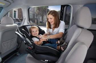 Mother installing her toddler into a Britax B-Safe car seat.